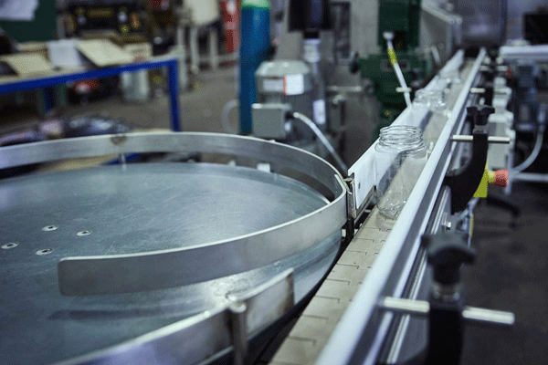 Slat chain conveyors moving containers from a rotary table to a filling machine