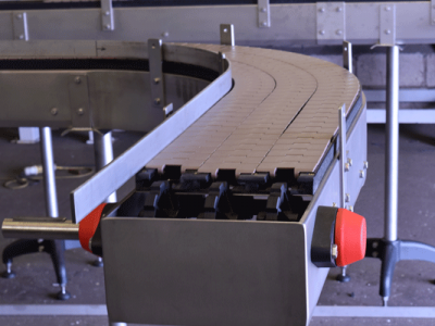 End view of slat chain conveyors curving to the left